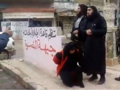 تجثو إمرأة خمسينية العمر على ركبتيها ليقوم عناصر من جبهة النصرة بإعدامها بتهمة الدعارة