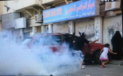 """أب يحاول حماية عائلته من الإختناق بالغازات المسيلة للدموع التي تواجه بها قوات الأمن المتظاهرين. الصورة: عن مستخدم تويتر <a href=""""http://https://twitter.com/daih_media/status/589415766778249217""""> Daih Media </a>"""