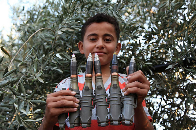 This 2012 photograph shows a Syrian boy holding an anti-aircraft rounds up to the camera and smiles in the newly liberated town of Marayan in northern Syria. Photograph by Syria Freedom, shared on flickr and used under (CC BY 2.0)