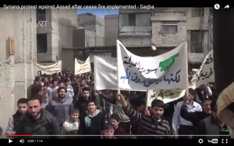 """لقطة مأخوذة من فيديو على <a href=""""https://www.youtube.com/watch?v=dK89j9uDvio"""">يوتيوب</a> لمظاهرة في سقبا بريف دمشق. تقول اللافتة:""""سوريا جميلة لكنها أجمل دون الأسد"""""""